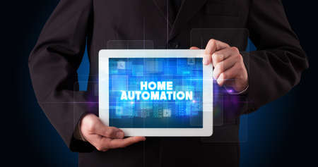 Photo for Young business person working on tablet and shows the inscription: HOME AUTOMATION - Royalty Free Image