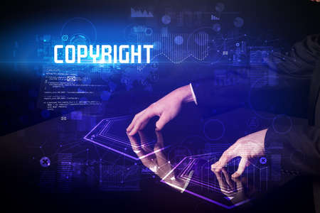 Foto de Hand touching digital table with COPYRIGHT inscription, new age security concept - Imagen libre de derechos
