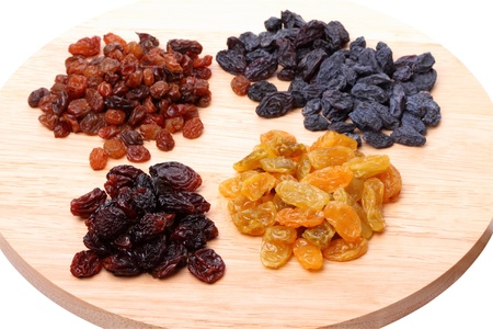 Four variety of raisins on a cutting board isolated on white backgroundの写真素材