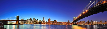 Photo pour New York City Manhattan skyline panorama with Brooklyn Bridge and Manhattan Bridge over East River at dusk illuminated with reflections and downtown skyscrapers viewed from Brooklyn. - image libre de droit