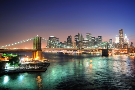 Photo for New York City Manhattan downtown skyline aerial view at dusk with skyscrapers lit over East River with reflections.  - Royalty Free Image