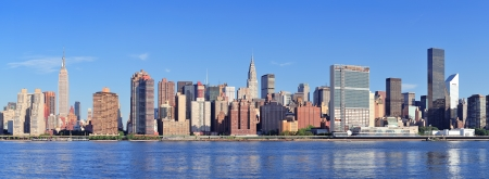 Manhattan midtown skyline panorama over East River with urban skyscrapers and blue sky in Ne