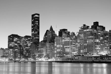 New York City Manhattan midtown skyline black and white at night over East River.