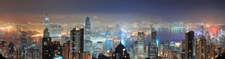 Hong Kong city skyline panorama at night with Victoria Harbor and skyscrapers illuminated by