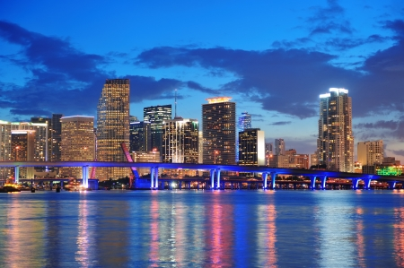 Photo pour Miami city skyline panorama at dusk with urban skyscrapers and bridge over sea with reflection - image libre de droit