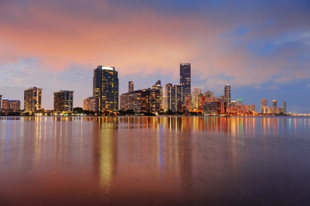 Photo pour Miami city skyline panorama at dusk with urban skyscrapers over sea with reflection - image libre de droit