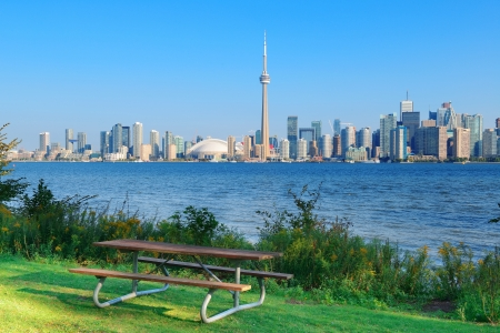 Toronto skyline in the day over lake with urban architecture viewed from park