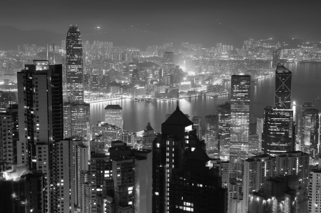 Hong Kong city skyline at night with Victoria Harbor and skyscrapers illuminated by lights o