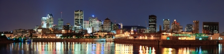Montreal over river panorama at dusk with city lights and urban buildings