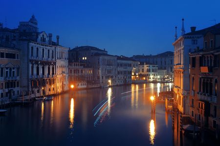Venice canal view at night with historical buildings. Italy.