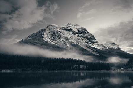 Photo pour Snow capped mountain with lake reflection in a foggy dusk in Banff National Park, Canada. - image libre de droit