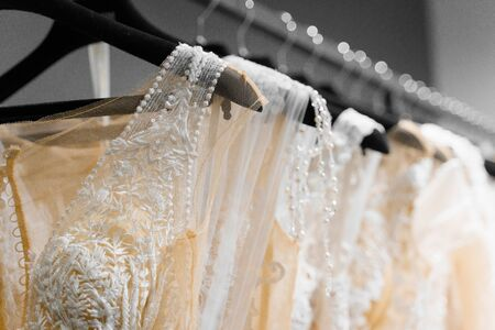 Cloth of wedding dresses made of silk chiffon, tulle and lace. Beautiful White cream bridal dress on hangers in wedding salon. Pearls and crystals pendants on the sleeves of a wedding dress