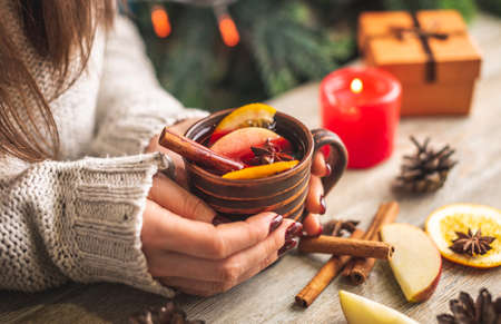 Photo pour Woman's hands in a warm sweater are holding a cup of aromatic hot mulled wine on a wooden table. Concept of a festive atmosphere and cozy winter mood. - image libre de droit