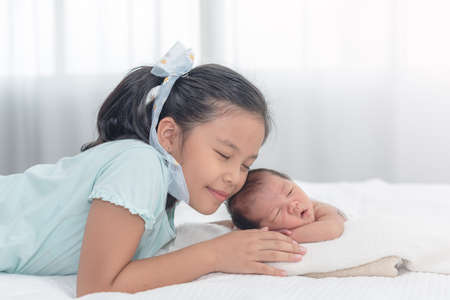 Photo for Sister happy welcome her little brother. Toddler kid meeting new sibling. Cute girl and new born baby boy relax in a white bedroom. Family with children at home. - Royalty Free Image