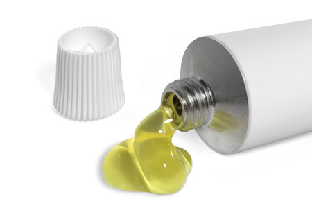 Open tube of white color with leaked yellow liquid