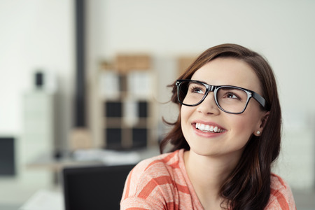 Smiling Young Woman Wearing Eyeglasses with Black Frames and Looking Up as if Daydreaming or Thinking of Something Pleasant