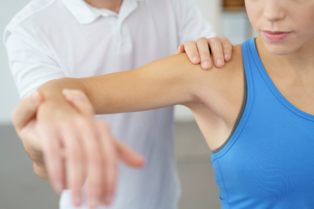 Photo pour Close up Professional Physical Therapist Lifting the Arm his Female Patient While Examining the Injured Shoulder. - image libre de droit