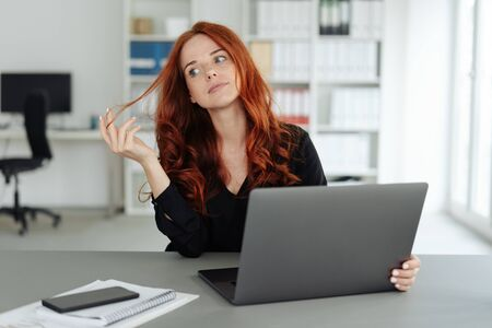 Foto de Thoughtful young businesswoman twiddling with her hair as she sits behind a computer at a desk in the office - Imagen libre de derechos