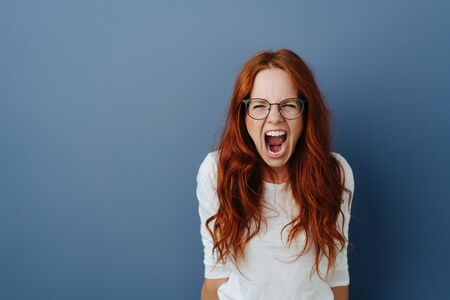 Photo for Angry young woman throwing a temper tantrum yelling at the camera with a furious expression over a blue studio background with copy space - Royalty Free Image
