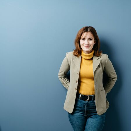 Photo for Happy pleased young woman with a beaming smile posing over a blue studio background with copy space in trendy jeans and jacket in square format - Royalty Free Image