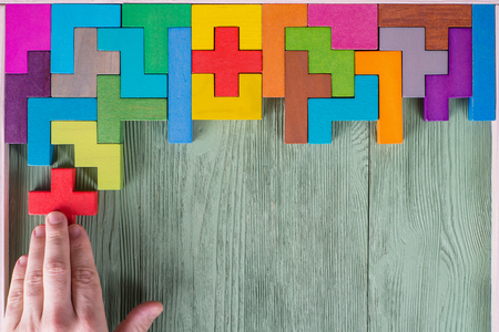Foto per Concept of decision making process, logical thinking. Logical tasks. Conundrum, find the missing piece of the proposed. Hand holding puzzle element. Background with colorful shapes wooden blocks - Immagine Royalty Free