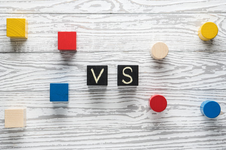 Photo for Letters VS on wooden background with copy space. The concept of making choice. Versus letters. White rustic wooden background and black cubes with letters VS. - Royalty Free Image