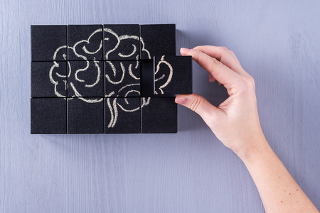 Photo for The concept of the human brain. Education, science and medical concept.  Brain drawn in chalk on black cubes. Female hands put in place the last element of the puzzle. - Royalty Free Image