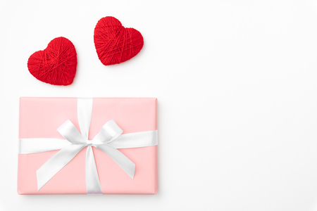Photo pour Valentine day idea composition: pink or coral gift box with white ribbon and small red hearts on white background. Top view. Love day concept flat lay. - image libre de droit