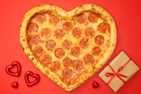 Foto de Heart shaped pizza pepperoni for Valentines day with gift box on red paper background. - Imagen libre de derechos