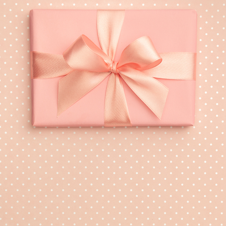Photo for Gift box luxury top view on living coral background with speckled, decorated with bow, creating festive atmosphere. Template used for 8 march women day, Mother day presents, gift cards. Flat lay. - Royalty Free Image