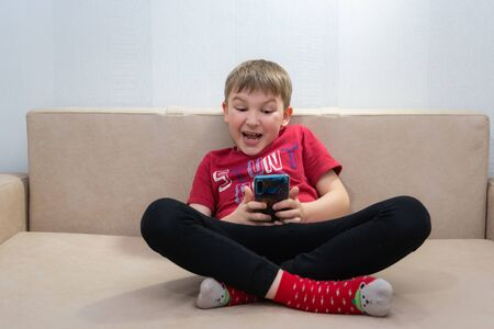 Photo pour The boy in the red shirt and red socks sitting on sofa and looks in the phone - image libre de droit
