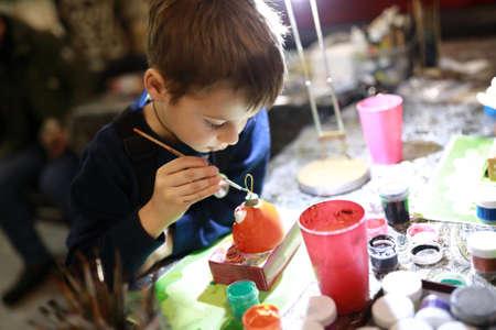 Foto de Boy painting a ceramic toy at workshop - Imagen libre de derechos