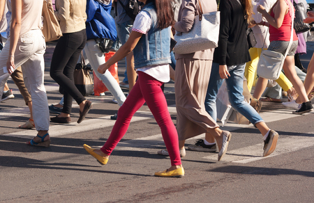 Photo pour feet of young pedestrians walking on the crosswalk on summer day - image libre de droit