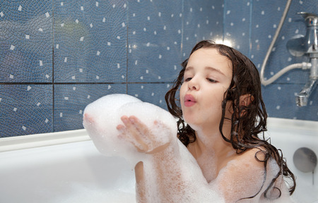 Photo pour little girl playing with soap bubbles in the bath - image libre de droit