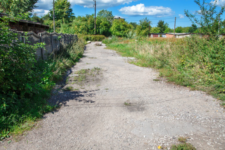 abandoned dirt road in the village on sunny summer day