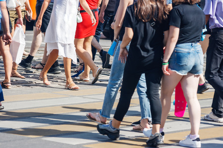 Photo for pedestrians crossing the road at a pedestrian crossing on summer sunny day - Royalty Free Image