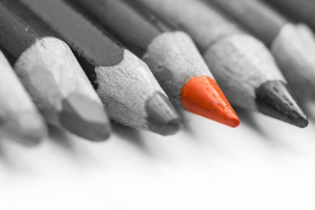 Foto de Closeup Of An Orange Crayon Standing Out Of A Larger Bunch Of Crayons - Imagen libre de derechos
