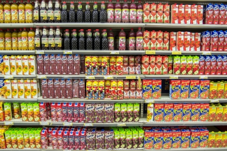 Supermarket Shelves Full With Different Natural Fruit Juice Bottles And Cartons
