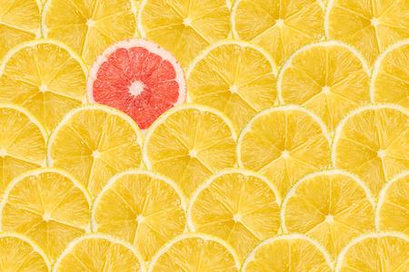 Photo pour One Pink Grapefruit Slice Stand Out Of Yellow Lemon Slices - image libre de droit