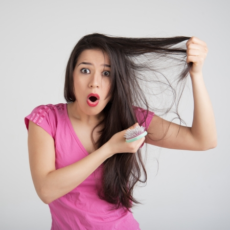 shocked woman losing hair on hairbrush
