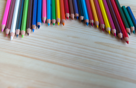 colored pencils lie on a wooden table