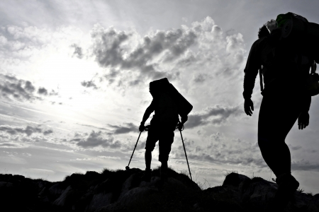 Silhouette of two hikers on a mountain ridge