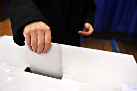 Close-up of a man's hand putting his vote in the ballot box