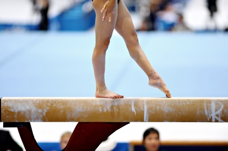 Photo pour Legs of a gymnast are seen during an exercise on the balance beam apparatus - image libre de droit