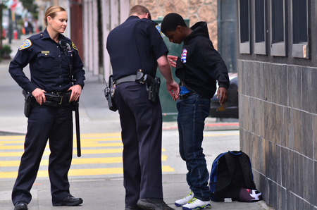 Photo for SAN FRANCISCO - MAY 15 2015:SFPD officers patdown black american man in San Francisco.Overall, Black Americans are arrested at 2.6 times the per-capita rate of all other Americans. - Royalty Free Image