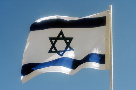 One Israeli national flag against blue sky.