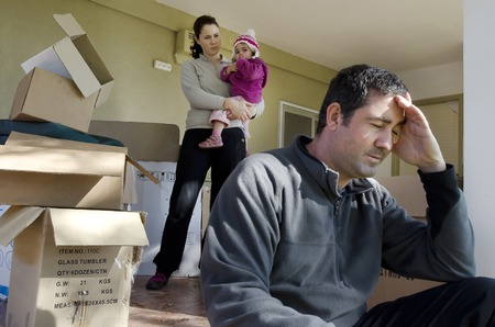 Young parents and their daughter stand beside cardboard boxes outside their home. Concept photo illustrating divorce, homelessness, eviction, unemployment, financial, marriage or family issues.