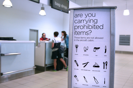 GOLD COAST, AUS - NOV 22 2014:Passengers in check in desk.For the safety and security air travelers airlines have prohibited certain items from brought onto airplanes in carry-on andor checked bags.