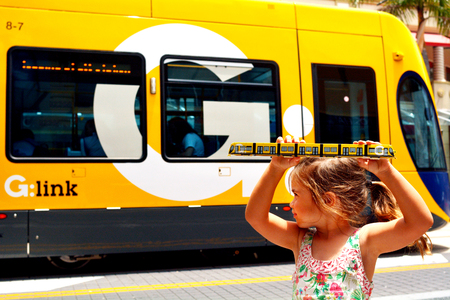 GOLD COAST, AUS - NOV 14 2014:Child Talya Ben-Ari age 04 hold a replica of Gold Coast Light Rail G in Surfers Paradise Av in Gold Coast Queensland, Australia.The line opened on July 2014 and it 13 Km 8.1 mi long.