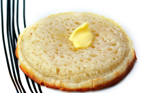 A buttered English crumpet close up. It's a griddle cake made from flour and yeast.